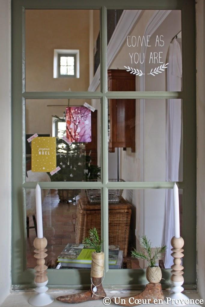 Bougeoirs 'Un esprit en plus' devant une fenêtre décorée pour les fêtes de Noël