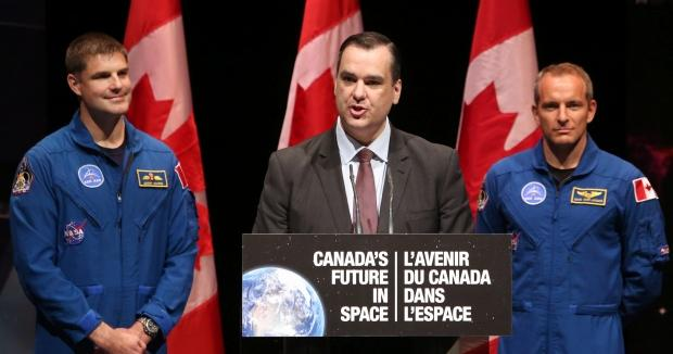 Industry Minister James Moore, flanked by Canadian astronauts Jeremy Hansen (left) and David Saint-Jacques (right), announces Canada's commitment to fly two Canadian astronauts to space by 2024 Tuesday. One is expected to fly in 2019, the other in 2024. (Fred Chartrand/Canadian Press)