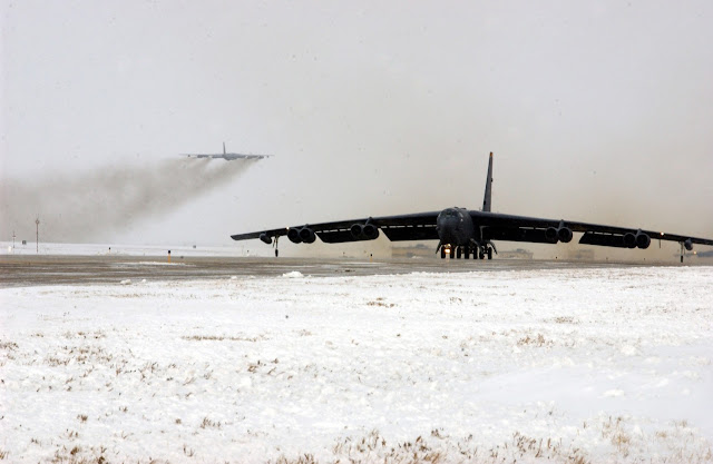 A B-52 Stratofortress taxis down the runway while another B-52 takes of in the background.