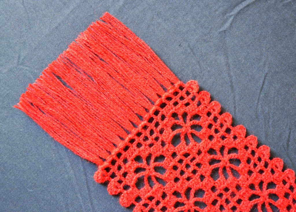 Diagonal view of Diamond Strike Scarf - short end of scarf showing 15 cm fringe after being trimmed. One and a half pattern rows of filet spiderweb pattern also visible.