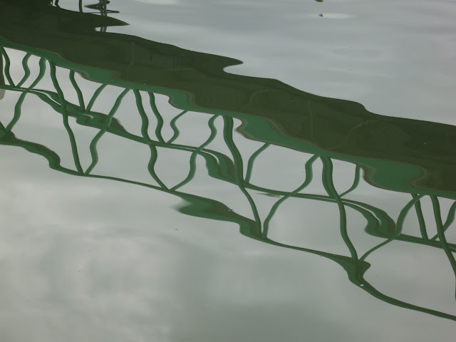 Rippled reflection of footbridge in water