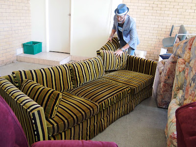 A man arranging the back cushions of a green, fawn and black striped sofa in a warehouse.