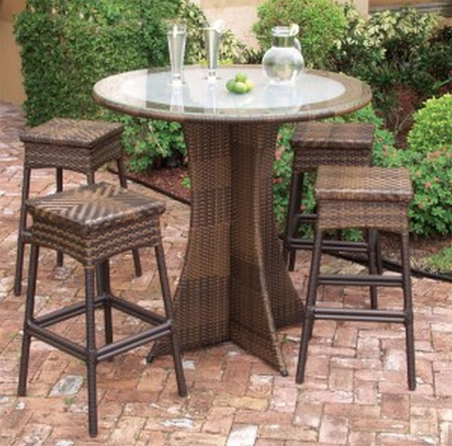 an exotic brown rattan plait round outdoor coffee table with classic leg and four wicker chairs surrounding it beside the green park