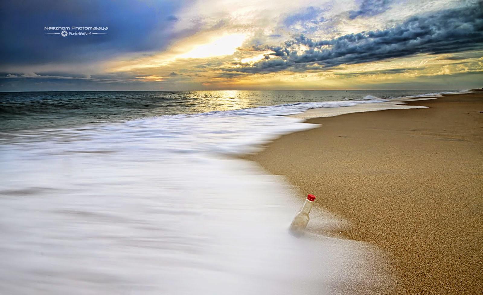 Sunrise dan botol dilanggar ombak di Pantai Batu Rakit