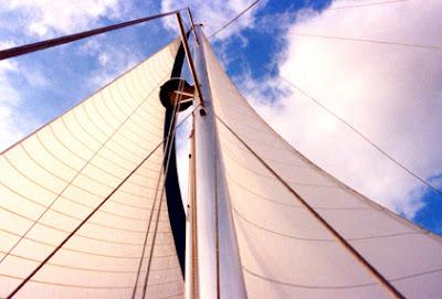White roller furling sails / aluminum spar against a partly cloudy sky