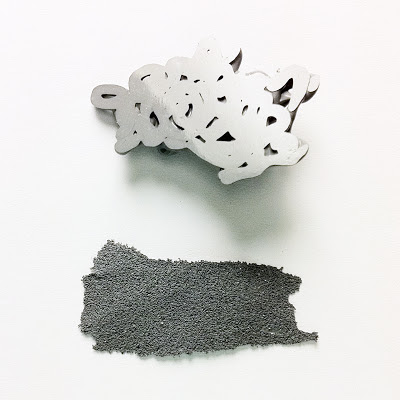 A composition of two grey casts one place above the other.  The lower piece is flat and looks like sandpaper and the upper is very polished yet consists of squiggles.