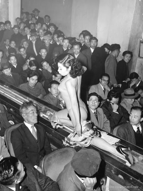 A stripper at a Tokyo striptease show is taken past the audience on a moving conveyor belt.