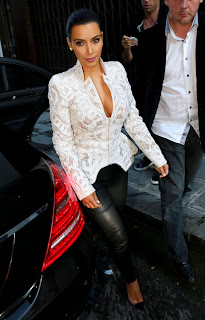 Kim Kardashian wearing a revealint top tight leather pants and hot black heels