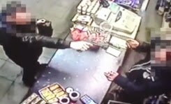 Fearless shopkeeper snatches gun out of robber's hand
