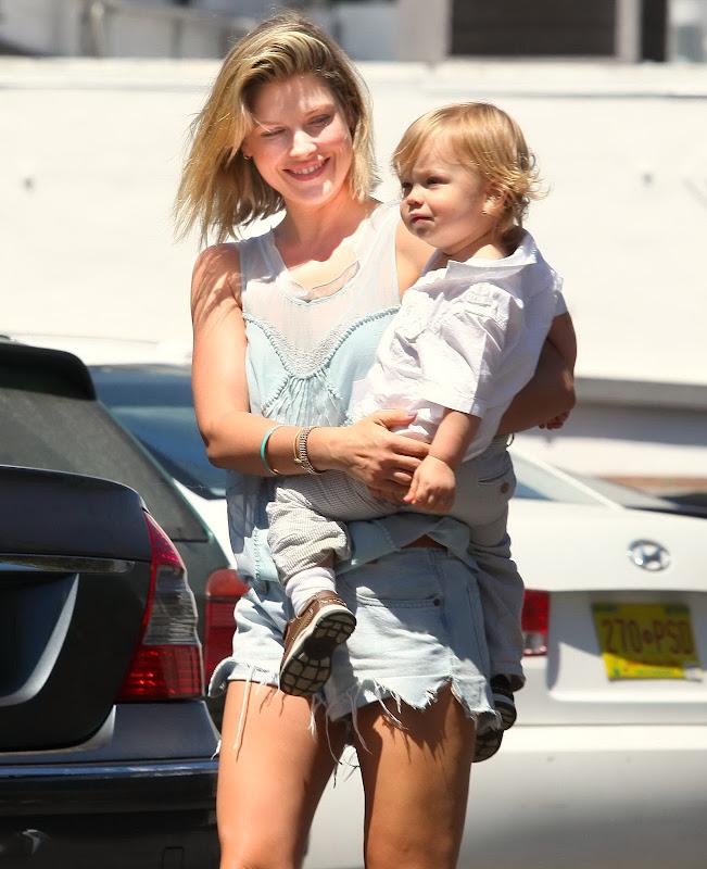 Ali Larter carrying her son