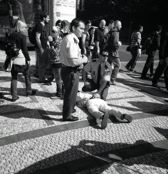 (上图一)中使馆官员对法轮功学员施暴被捷克警察铐住(明慧网)