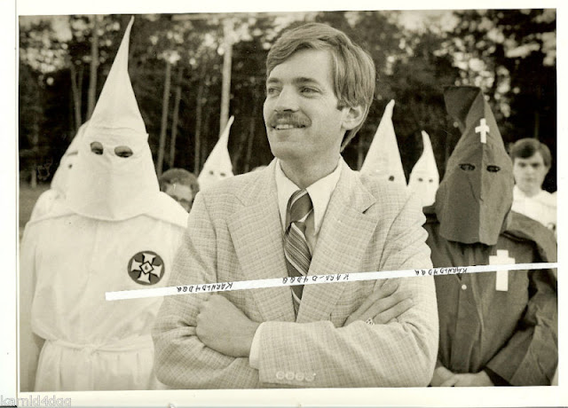 David Duke attending a Louisiana Ku Klux Klan rally in 1979 (Photograph by Michael P. Smith). A mustachioed Duke is in the foreground wearing a light colored tweed suit and striped tie. His arms folded, he is grinning, and looking off into the distance. Behind him are several hooded and draped members of the Ku Klux Klan.