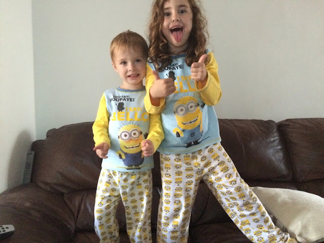 Boy & girl wearing matching minions pyjamas with thumbs up