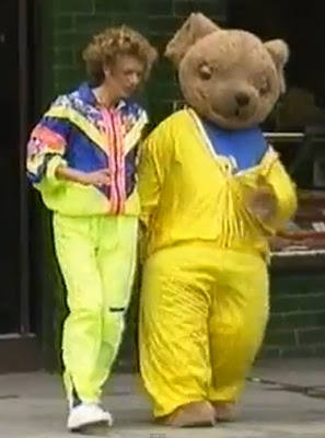 Lizzie Webb and Joggy Bear wear bright yellow nineties-style tracksuits