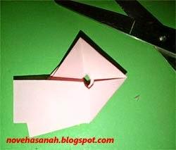buatlah lubang dengan gunting di tengah-tengah lipatan kertas