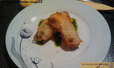 Fiori di zucca fritti ripieni di alici e formaggio, gamberetti e formaggio, serviti su un pesto di rucola