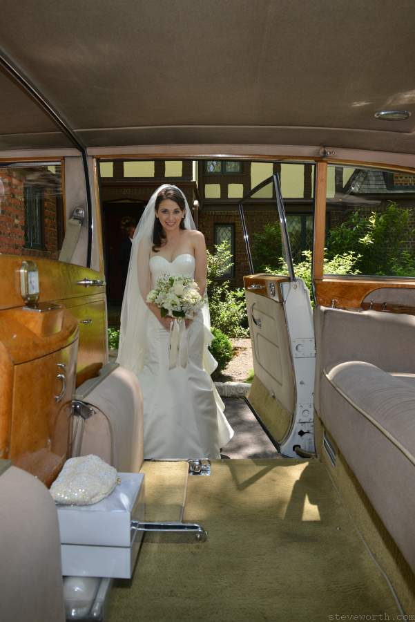 Bride looking trough the doors of the Rolls Royce