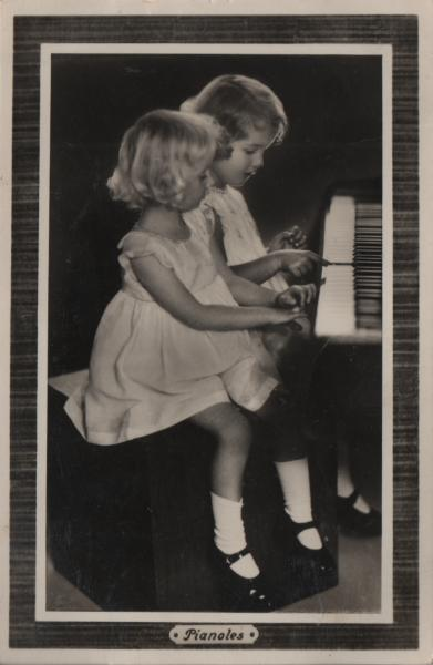 two little girls playing the piano