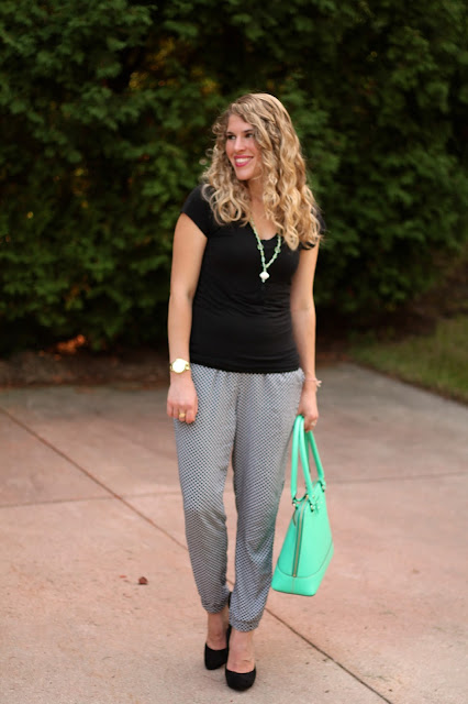 black top and printed joggers, heels and mint Kate Spade bag