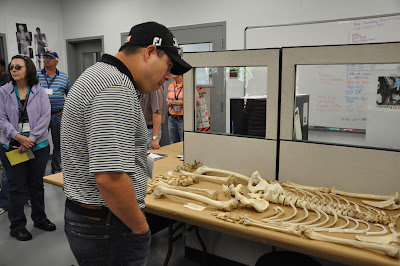 A teacher examines a skeleton at the Southeast Texas Applied Forensic Science Facility.