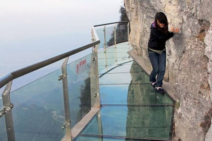 Jutting out from a sheer cliff 1,430 meters high, the glass skywalk in Zhangjiajie National Forest Park offers sightseers terrifying thrills and clear view of the mountains below as they tread nervously across the 60 meter long bridge encircling the vertical cliffs of Tianmen Mountain in Hunan province. The 3ft-wide, 2.5in thick glass walkway is so scary that sightseers are requested to wear cloth slip-ons over their shoes when they cross the skywalk, presumably to make the job easier for the cleaners.