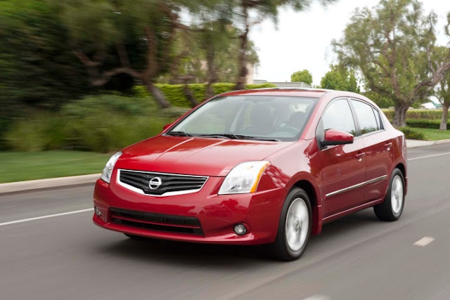 Front 3/4 view of red 2011 Nissan Sentra sedan driving on suburban street