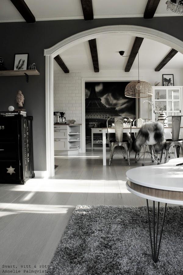 matsal, matsalsbord, matstolar, plåtstolar, plaststol, vitt, grått, fototapet eiffeltornet, fårskinn på stolar, container, plåtskåp, artprint, fjäder, feather, konsttryck, illustration, svart fågel, svartvita motiv på tavlor, inspiration tavlor, tavla, svart, svarta, vit, vita, vit parkett, parkettgolv, tarkett, plankgolv, valv mellan rum, vitt valv, takbjälkar, gråmålad vägg, matt grå färg på väggen i vardagsrummet, buddha figur, böcker, dekoration, inredning, inspiration, interior, interiör, home, inspo, hylla med tavlor, hth kök, moccamaster, vitrinskåp, vitt soffbord, öppen planlösning