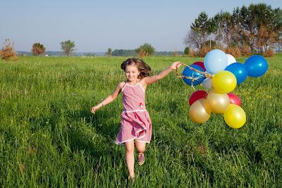 Niña juega en los jardines con sus globos de colores