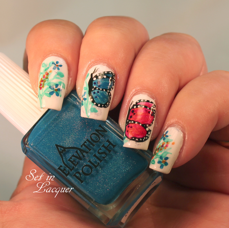 Butterfly nail art with floral accents