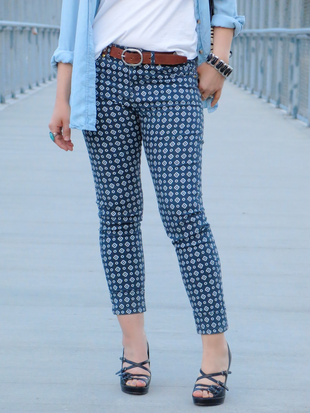 styling printed pants with a chambray shirt, strappy platform shoes, and a metal and leather bracelet
