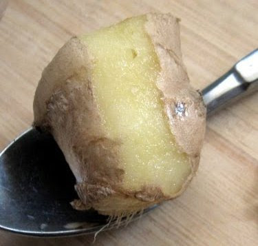 peeling fresh ginger with a spoon