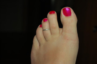 Man with pink painted toes and a toe ring