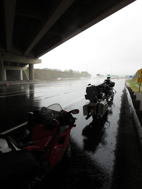 Motorcycles waiting out the rain.