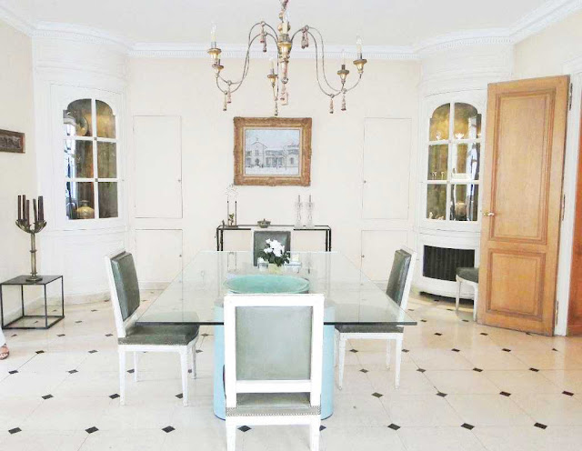 Dining room in a Paris apartment with a glass table,  louis xvi chairs, built in curio cabinets and a white tile floor