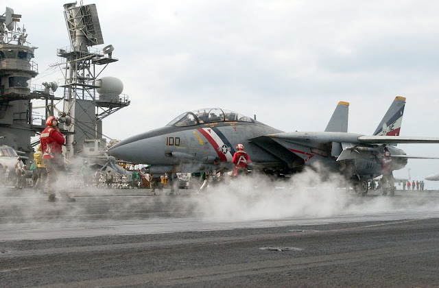 "A flight deck crewmember guides an F-14D ""Tomcat"" assigned to the ""Bounty Hunters"" of Fighter Squadron Two (VF-2) onto one of four steam driven catapults on the ship's flight deck."
