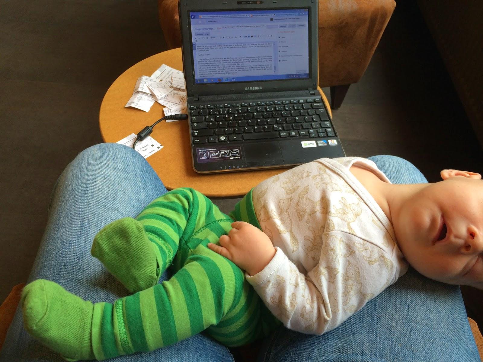 Baby liegt beim Schreiben am Laptop