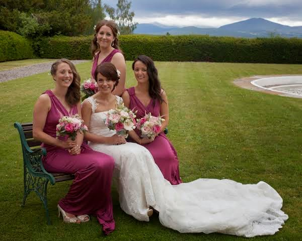 The bridal party pose for a photograph in the grounds of the estate