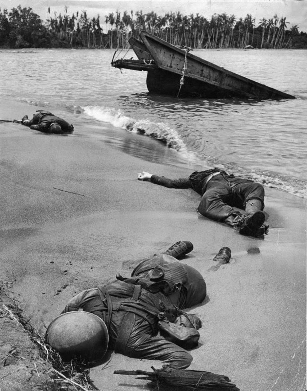 Bodies of dead American soldiers near half sunken sanding craft on Buna beach. Due to the number of dead bodies on the beach, the Allies nicknamed it