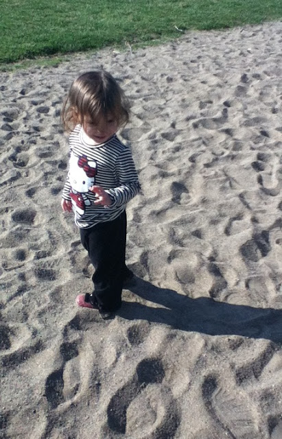 Toddler in the sand at the park.
