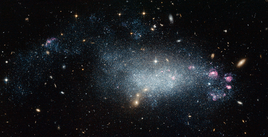 This image from the NASA/ESA Hubble Space Telescope shows a cosmic oddity, dwarf galaxy DDO 68.  This ragged collection of stars and gas clouds looks at first glance like a recently-formed galaxy in our own cosmic neighbourhood. But, is it really as young as it looks?  Credit:  NASA, ESA  Acknowledgement: A. Aloisi (Space Telescope Science Institute)