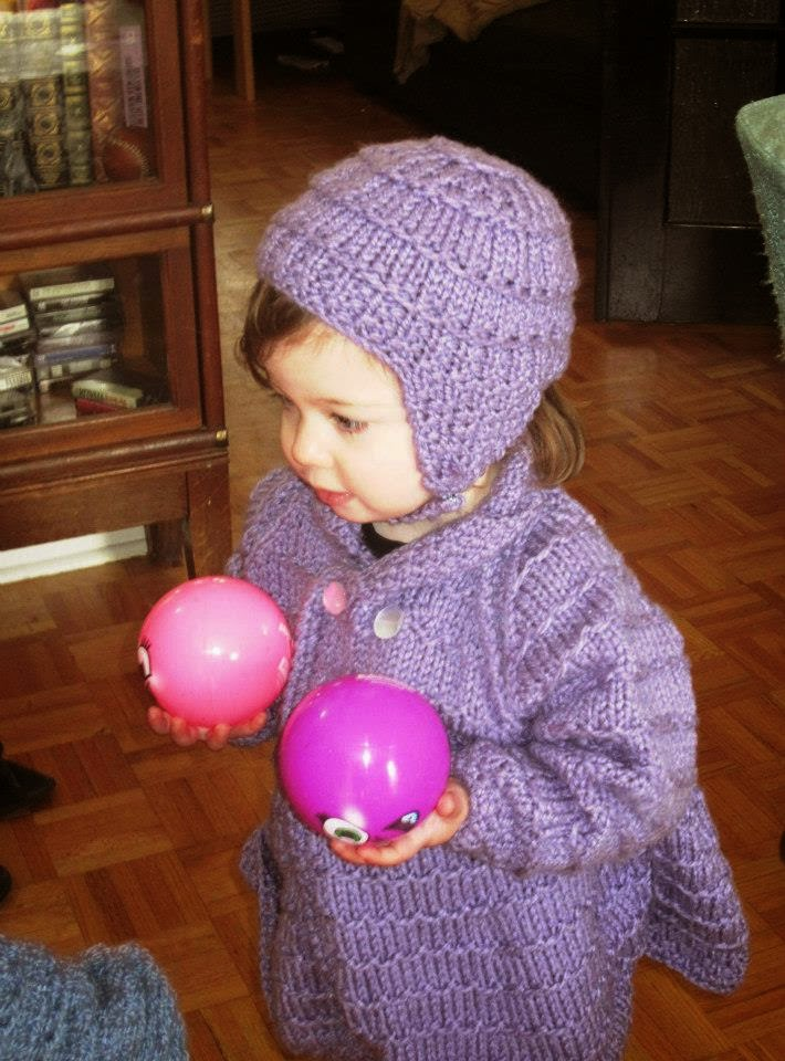 toddler in hand knit purple bonnet and sweater