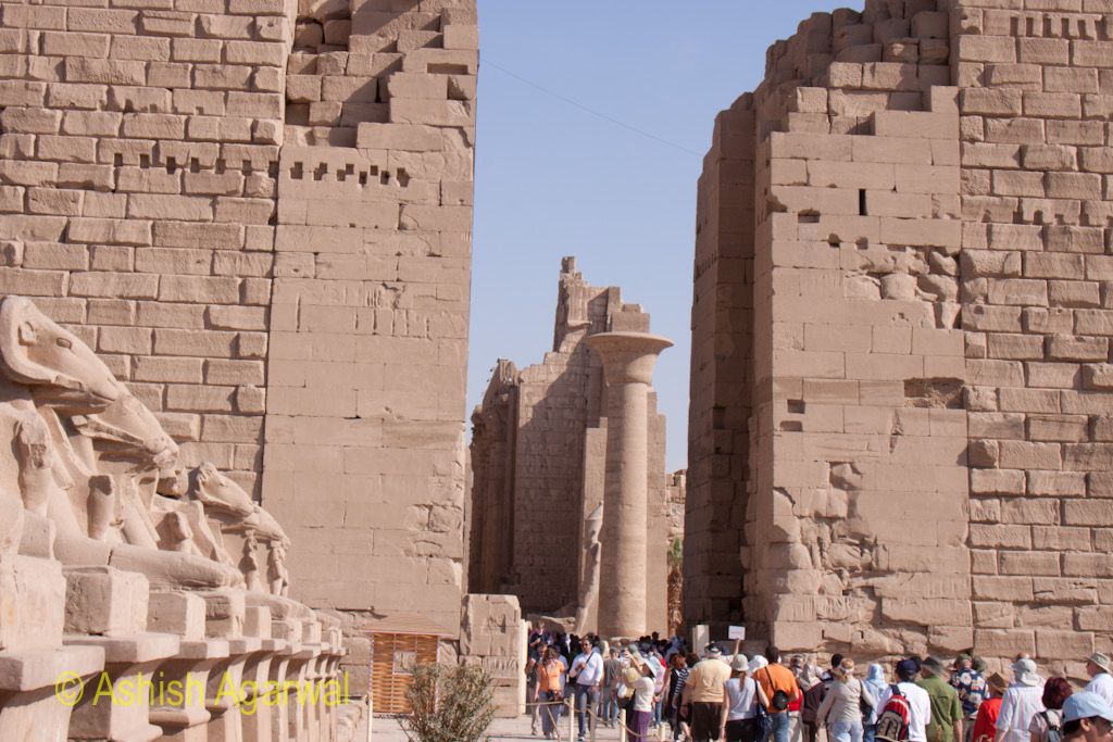 People walking through the front pylon of the Karnak temple at Luxor