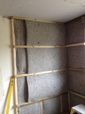 Second layer of sheepwool internal insulation being fitted to the wall