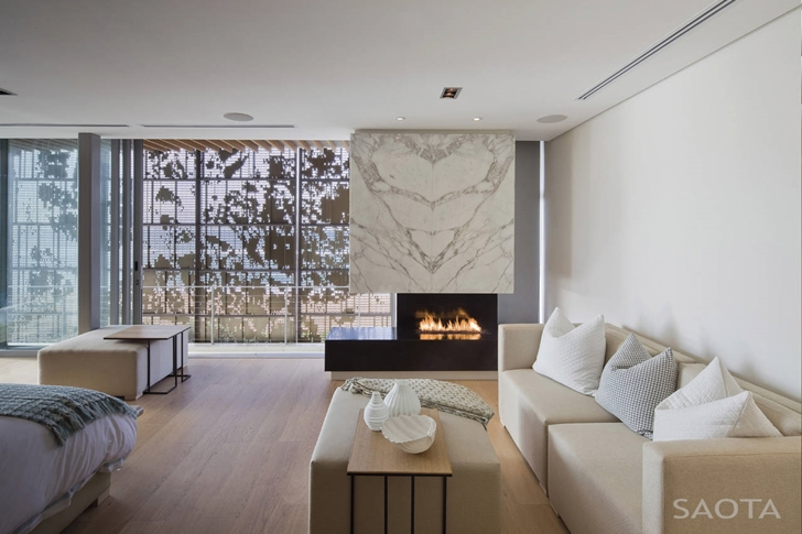 Bedroom fireplace in African modern villa in Durban by SAOTA
