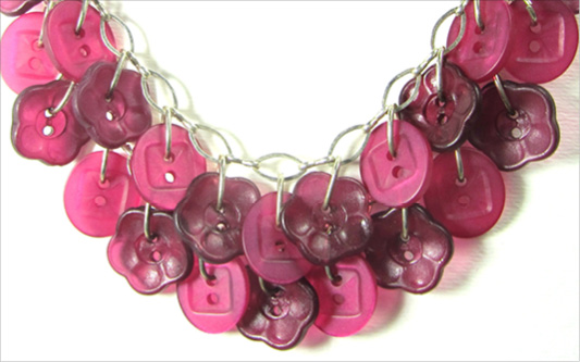 Pretty necklace has layers of pink buttons hanging from silver chain