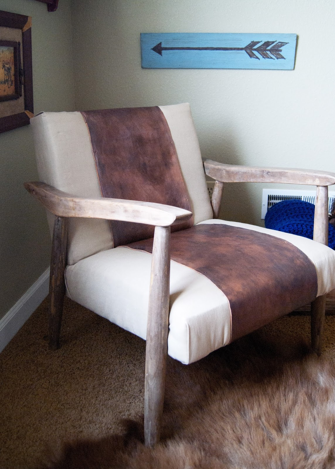 Mid century chair gets a makeover with linen and leather. Arrow sign in background is awesome!