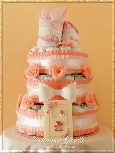 Torta di pannolini decorata con fiocchi e rose