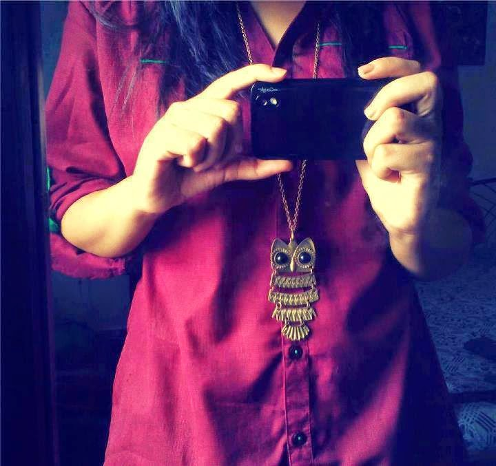 girl hide face with cam in maroon suit