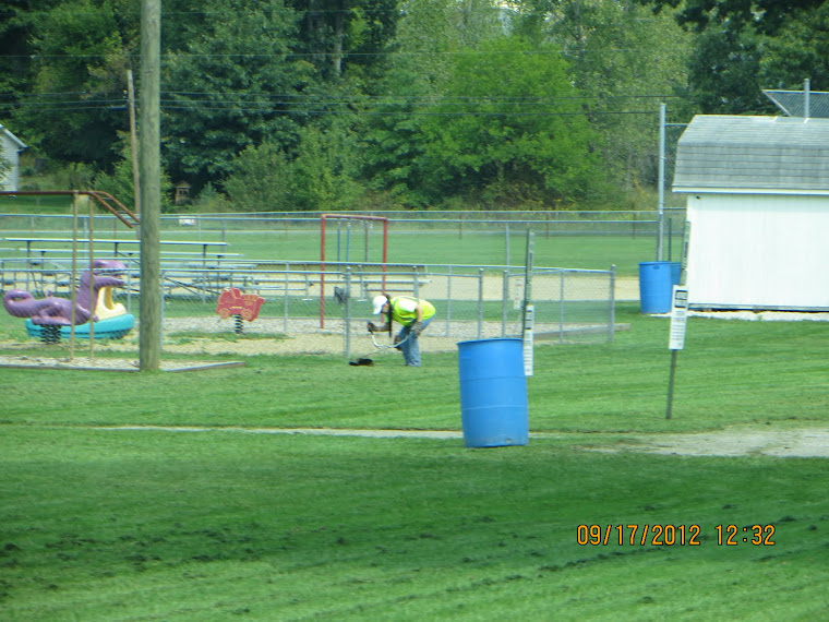 The BLV ballfield grass is so short,the clerk's daughter has to look close to get her Mow Money.