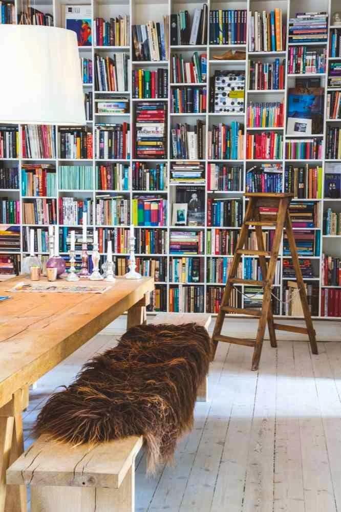 Biblioteczka na cąłej ścianie, drewniana ławka przykryta futrem, drewniany prosty stół, drabina przy biblioteczce